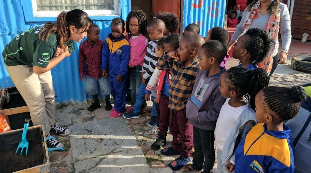 Pasante de Nutrición en Sudáfrica le enseña a niños locales a cómo cultivar un huerto.